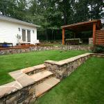 Stone terracing creates flat play areas out of a steeply sloping lawn.