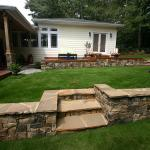 A deck and a stone wall create usable space out of a steeply sloping lawn.