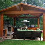 A pavilion provides protection for an outdoor kitchen and seating area.