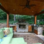 A covered outdoor living area features a kitchen and fireplace.