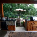 A grill, sink, gas burner, and storage cabinets highlight this outdoor kitchen.