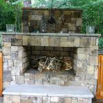 A stone-faced fireplace is a focal point in covered outdoor living area.