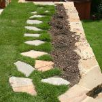 A stepping stone path leads to a spa, built into a terraced lawn.