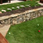 A stone retaining wall with steps between terraces, and stone path to spa.