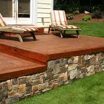 A ground-level deck and stone retaining wall create level space for furniture.