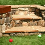 Stone steps provide easy access between levels in this terraced backyard.