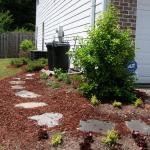 Stepping stones are used to create a pathway to a trash can storage area.