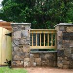 Matching stone pillars and gates provide entry into neighboring backyards.