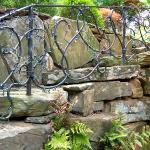 Large stones create a naturalized stairway to the upper level of this property.