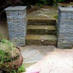 Stone pillars flank stone steps and walkway.