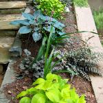 A stone-capped planter creates a wall to edge one side of a stone stairway.