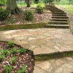 A stone landing creates a patio area at the midpoint of this stepped pathway.