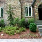 A planted bed softens the texture of the stone-fronted house.