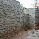A dramatic curved wall made out of stacked stone provides privacy at this home.