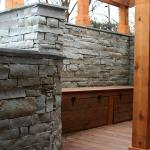 A custom bench with storage was built in an inset in a stacked stone wall.