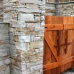Custom-crafted doors screen an outdoor storage area set into a stone wall.