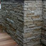 The Yard Artist constructed a stacked stone wall and elevated wooden walkway.