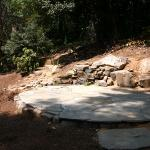 A circular stone patio provides a quiet spot next to a waterfall and stream.